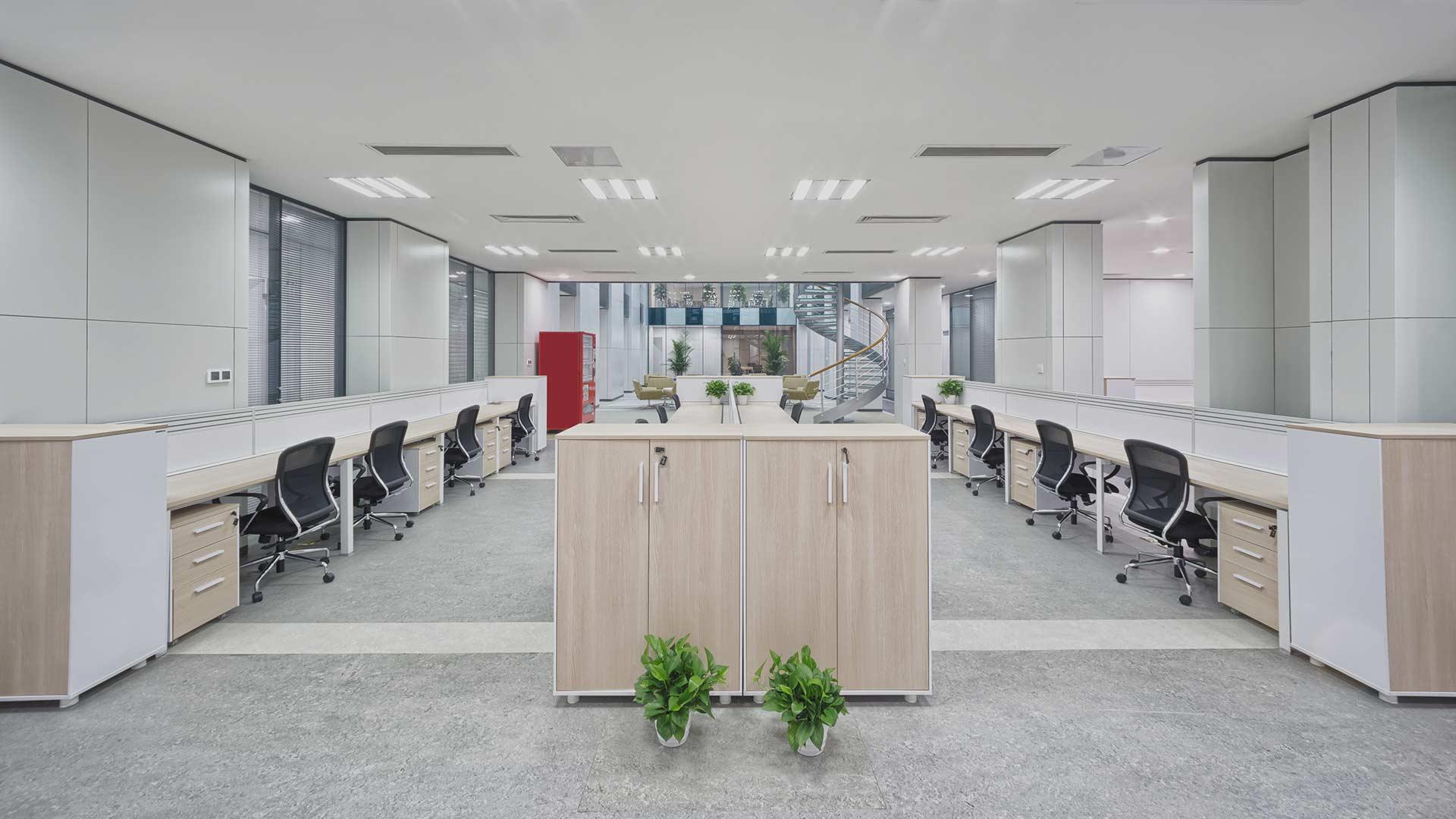 Innvendig kontorlokale med lange arbeidspulter og gulvbelegg på gulv